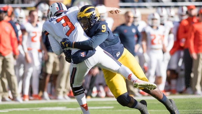 Michigan linebacker Mike McCray tackles Illinois quarterback Jeff George Jr. in the first quarter.