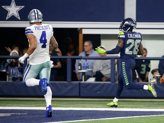 Dallas Cowboys' Dak Prescott (4) follows behind watching as Seattle Seahawks' Justin Coleman (28) returns a Prescott interception for a touchdown in the second half of an NFL football game, Sunday, Dec. 24, 2017, in Arlington, Texas. (AP Photo/Michael Ainsworth)