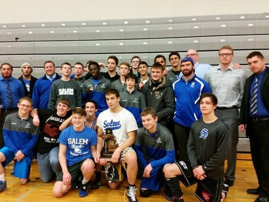 Salem's varsity wrestling team celebrates after winning the Division 1 district at Plymouth High School Wednesday night.