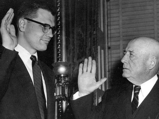 This photo provided by Rep. John Dingell's office, shows the congressman being sworn in by mentor and Speaker of the House Sam Rayburn of Texas in 1955.
