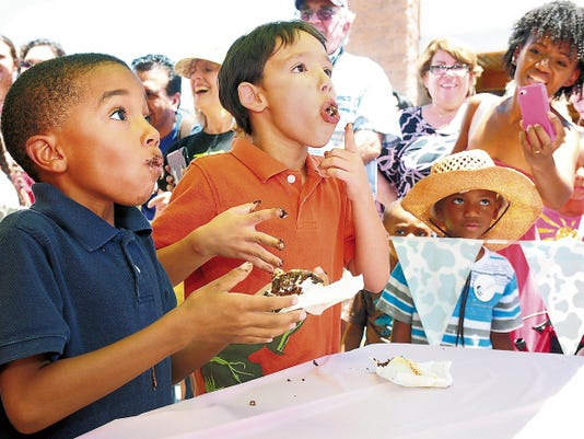 Amonte Craddock, left, and Oren Whalen, chew and swallow ice cream sandwiches as fast as they can as they compete in the first heat of an ice cream sandwich eating competition at a recent Ice Cream Sunday celebration at the New Mexico Farm & Ranch Heritage Museum.
