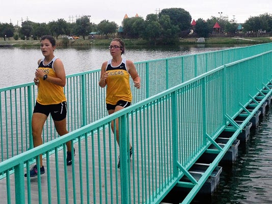 Madison Varnier, left, and Summer Clifton run across the riverwalk bridge Saturday during the Elks-Ron Singleton Invitational. at the Lake Carlsbad Beach Park.