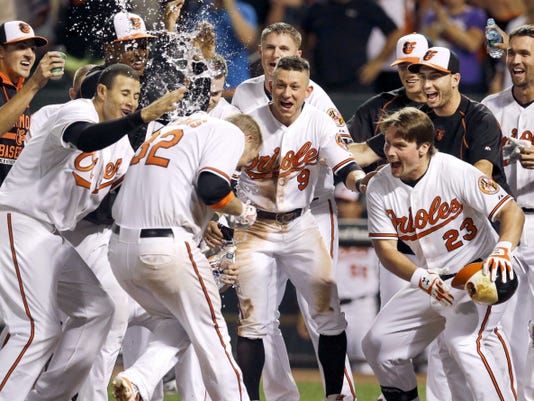 Teammates celebrate as Baltimore Orioles' Matt Wieters (32) crosses home plate after hitting a solo home run in the 11th inning against the Atlanta Braves on Monday in Baltimore. Baltimore won, 2-1, in 11 innings.