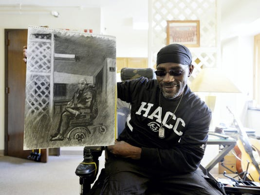 "Brad ""Smitty"" Smith holds up a self-portrait he drew for class on a recent Friday in his York apartment."