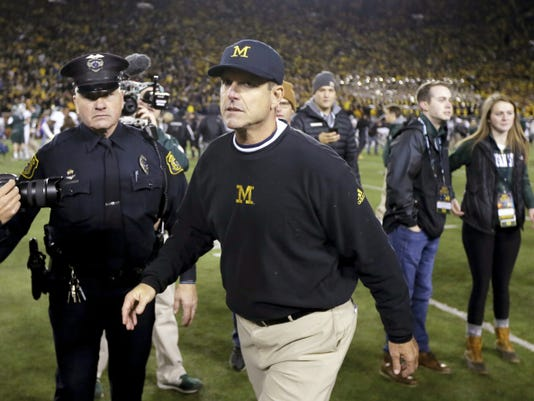 Michigan head coach Jim Harbaugh walks off the field after their 27-23 loss to Michigan State in a game Oct. 17 in Ann Arbor, Mich.