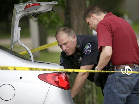 Investigators look into the trunk of car that was struck by a bullet Saturday in the 900 block of South Kensington Drive in Appleton. A police officer and a man who stopped to help the officer were shot during a struggle with a suspect. A witness said the suspect died after shooting himself in a driveway.
