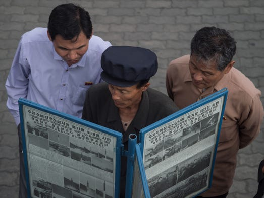 People gather at a street-side newsstand in Pyongyang