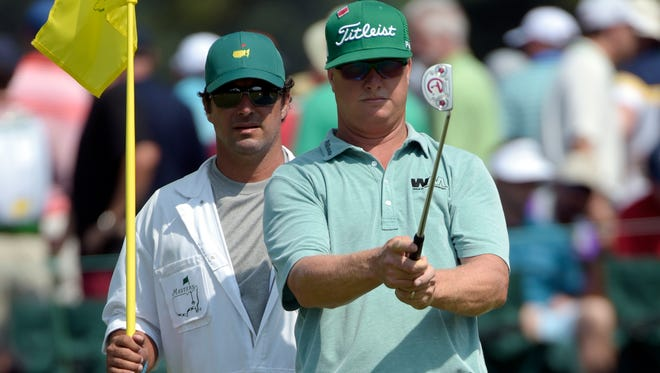 Charley Hoffman lines up a putt with caddie Brett Waldman on the 17th green during the first round of The Masters.