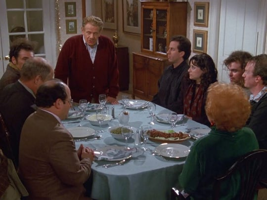 Frank Costanza (Jerry Stiller), standing, begins the Festivus celebration. Feats of Strength are just around the corner.