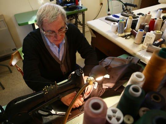 Mario Simoni works on a pair of trousers at Mario's