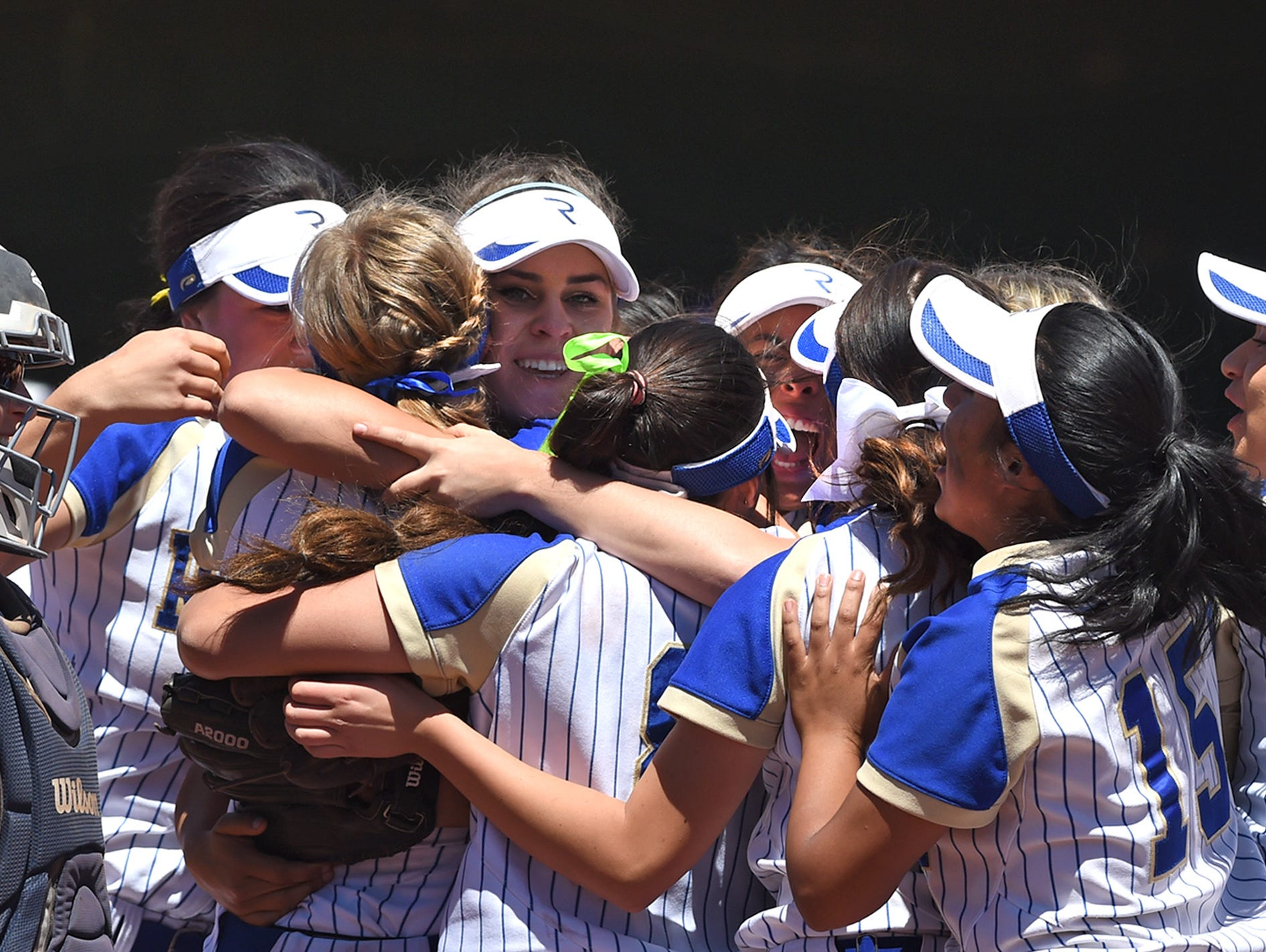 The Reed softball team gathers around pitcher Julia Jensen after defeating Spanish Springs 6-0 for the Northern Region title.