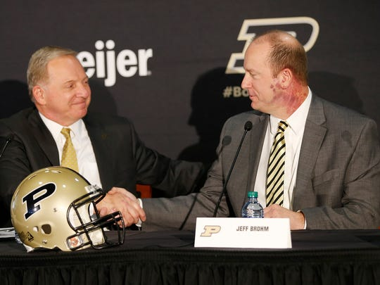 Athletic Director Mike Bobinski shakes hands with Jeff Brohm after introducing him as new head football coach Monday, December 5, 2016, at Purdue University. The former Western Kentucky football coach replaces Darrell Hazell, who was fired six games into the season.