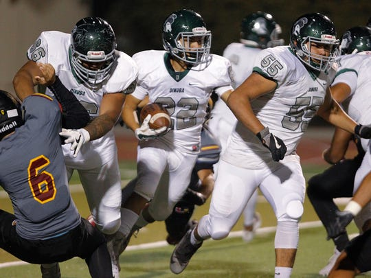 Dinuba's Luis Colunga looks for running room past Tulare Union defenders in a non-league matchup Friday, Sep. 29, 2017 in Tulare, Calif.