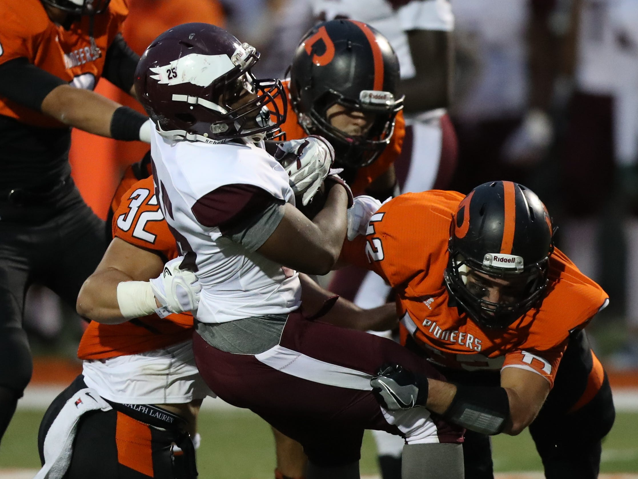Romulus' tackled by Dearborn defenders Friday at Dearborn.