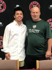 Jacob Cochran with Northern Michigan/U.S. Olympic Greco-Roman Training Center coach Rob Hermann, following Cochran's recent signing event at Tate High School.