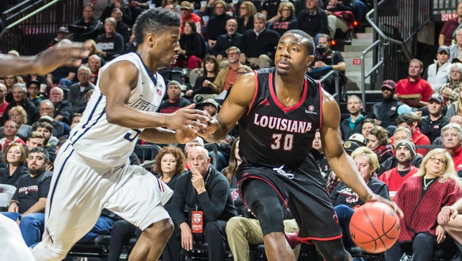 The Cajundome seats behind him are full as UL's Johnathan Stove drives the baseline in Thursday night's win over South Alabama.