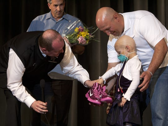 Pine View boys basketball coach Darrell Larsen hands four-year-old Jessica Schmitt a pair of pink basketball shoes as her father, Cody Schmitt helps her out during an assembly at Pine View High School.