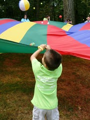 Campers play with a parachute at Camp Mighty Oaks, Willamette Valley Hospice?s summer camp for families who have lost a loved one. This year the camp will be held Saturday, July 26, 2014.