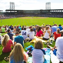 Fans watch from the outfield grass a 2014 spring-training game between the Arizona Diamondbacks and the Chicago Cubs at Cubs Park.