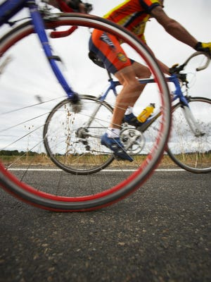 Road cyclist, bicycle wheel in foreground (surface level) [Via MerlinFTP Drop]