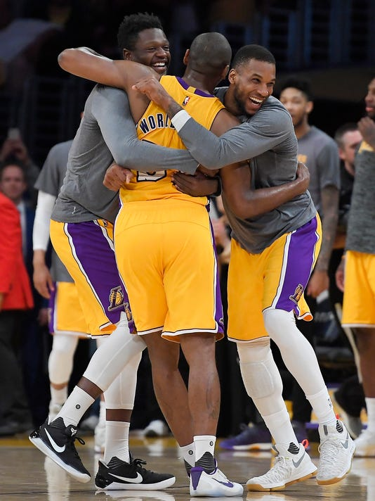 Los Angeles Lakers forward Metta World Peace, center, is hugged by forwards Julius Randle, left, and Thomas Robinson after the Lakers defeated the New Orleans Pelicans 108-96 in an NBA basketball game, Tuesday, April 11, 2017, in Los Angeles. (AP Photo/Mark J. Terrill)