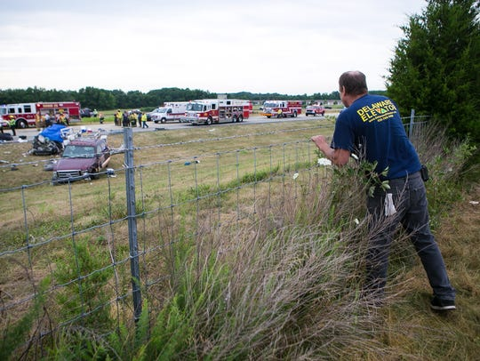 A man looks over a fence at an accident scene on Del. 1 south of Middletown that claimed the lives of 5 members of the same family July 6.