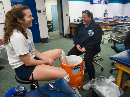 University of West Florida Head football trainer Melanie Burt, right, shares a laugh with volleyball player, Katy Kuhlmeier, during therapy in mid-November.