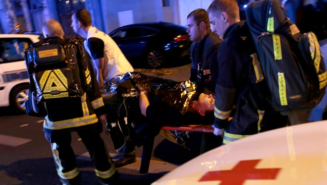 A picture made available on  shows an injured woman being transported by paramedics after being rescue at Bataclan Music concert Hall in Paris.