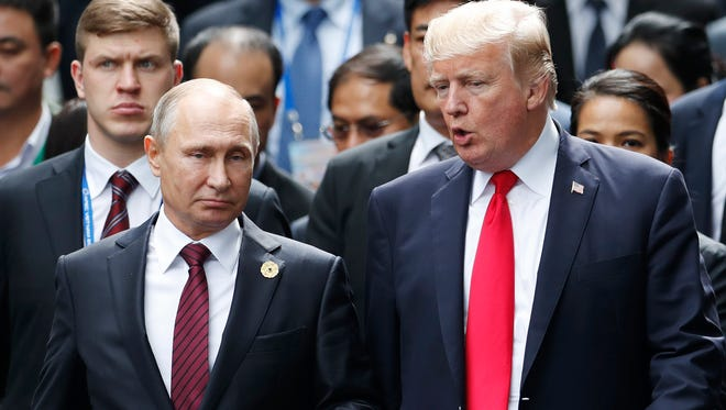 President Trump and Russian President Vladimir Putin talk during a photo session at the APEC Summit in Danang, Vietnam.