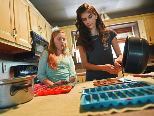 Abby Shay Neff, 14, of Recycled Rainbows, pours melted down donated crayons into a mold to make new crayons as her sister Riley, 11, looks on Wednesday, July 27, 2016, at her home in Sioux Falls.