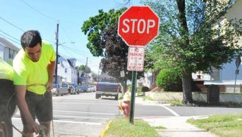 A package of ordinances has been introduced to specify how close motorists can park to borough stop signs by location. Here Daniel Goffredo paints a curb on Willis Road in North Arlington.