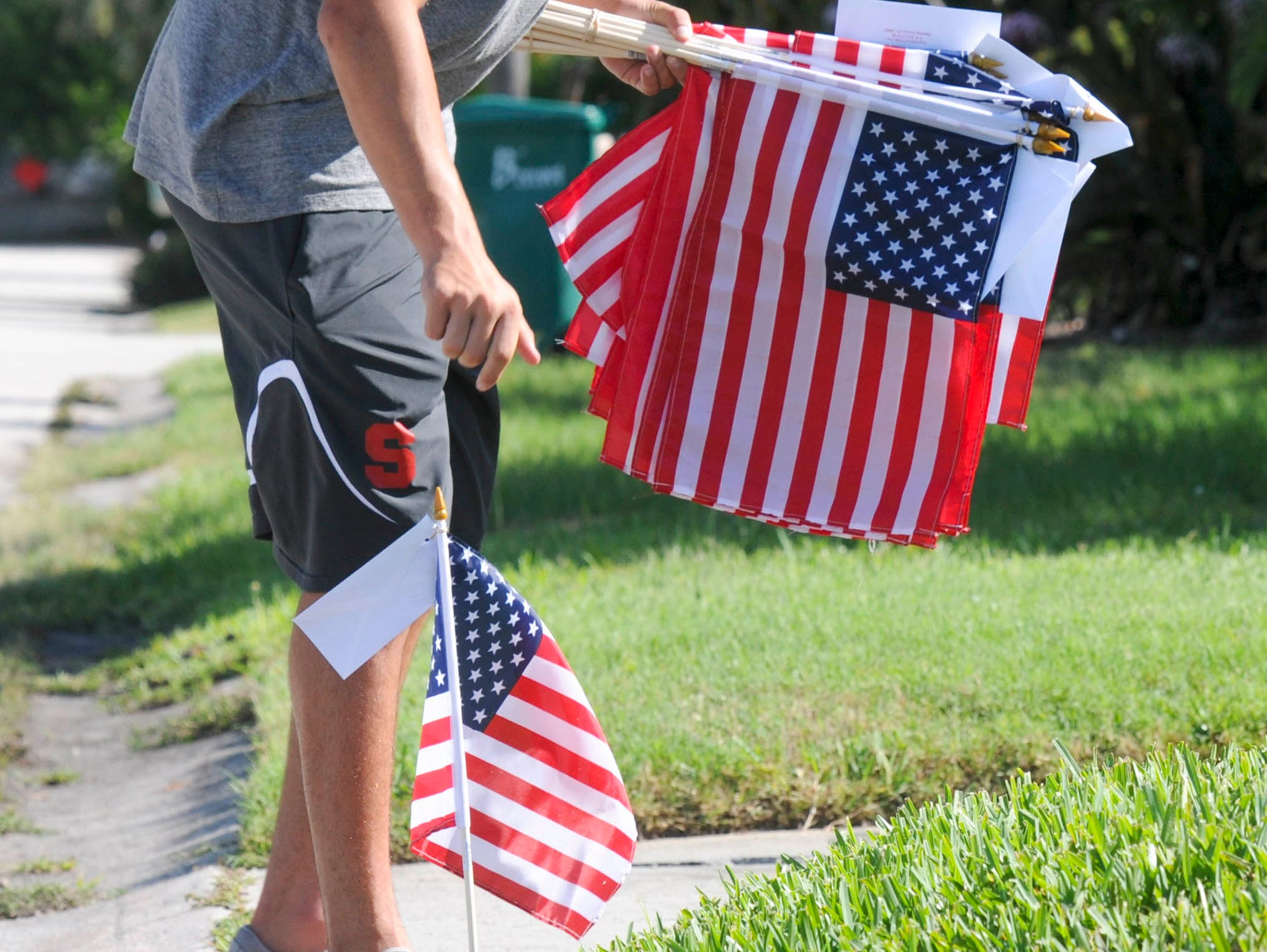 Cameron Saydo helps set out American flags Thursday morning in Satellite Beach. Students from Satellite High's football and ROTC squads help distribute American flags as part of a fundraiser for the school.