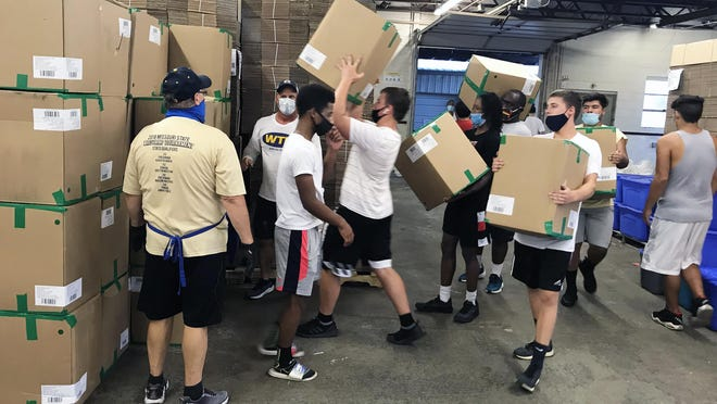 Members of the William Chrisman High School football team help the Community Services League by unloading 700 boxes that contain a half million socks. They will be distributed to those in need throughout the metro area and ranging as far as Manhattan, Kan., to Columbia, Mo. The socks were donated by Bombas Socks, which donates a pair of socks for each pair purchased.