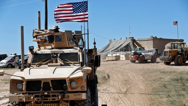 A U.S. soldier, left, sits on an armored vehicle behind a sand barrier at a newly installed position near the tense front line between the U.S-backed Syrian Manbij Military Council and the Turkish-backed fighters, in Manbij, north Syria, on April 4, 2018.