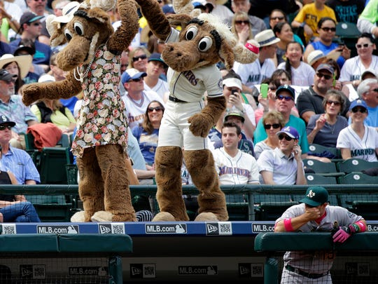 """Moose,"" the Seattle Mariners mascot, dances with a mascot dressed as his mother on the roof of the Oakland Athletics visitor's dugout  during a baseball game on Mother's Day, Sunday, May 10, 2015 in Seattle. (AP Photo/Ted S. Warren)"