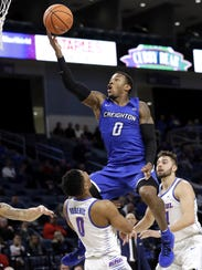 Creighton guard Marcus Foster, top, drives to the basket