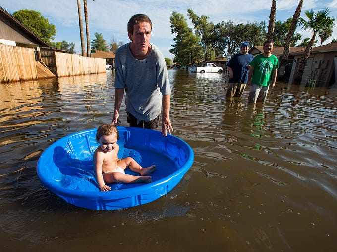 Arthur Lyman, pushes a friend's baby, Alyssa Guarino,22 months, in a plastic pool down his flooded neighborhood at the intersection of E. Glade Ave. and S. Allen in Mesa, Tuesday, September 9, 2014.  The area was inundated with water after the deluge on Monday.  Wayne Guarino, Alyssa's uncle, third from left, and Michael Rodriguez, right, are in background.