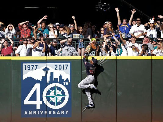 Cleveland Indians center fielder Greg Allen climbs the wall as fans cheer and look up for a home run ball hit by Seattle Mariners' Robinson Cano in the eighth inning of a baseball game Saturday, Sept. 23, 2017, in Seattle. (AP Photo/Elaine Thompson)