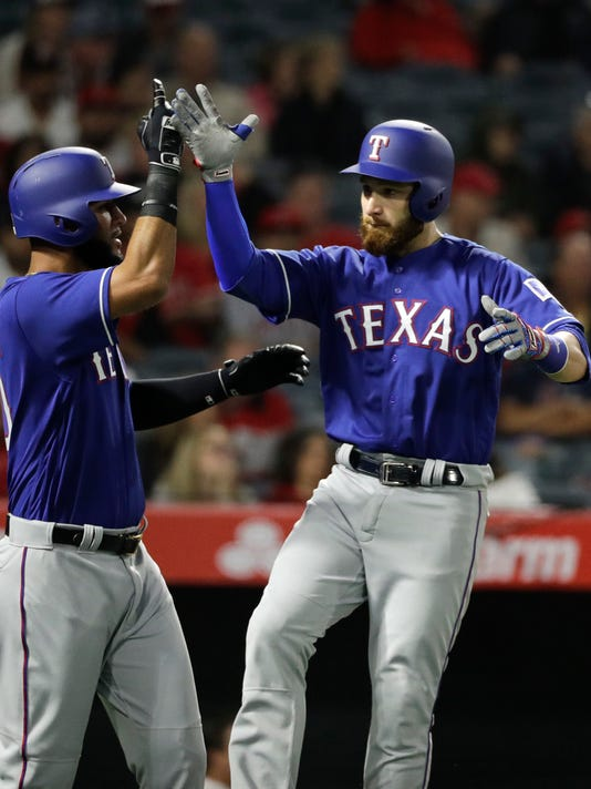 Texas Rangers' Jonathan Lucroy, right, celebrates his three-run home run with Nomar Mazara during the third inning of a baseball game against the Los Angeles Angels, Tuesday, April 11, 2017, in Anaheim, Calif. (AP Photo/Jae C. Hong)