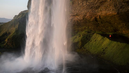 A woman looks up from behind the Seljalandsfoss waterfall