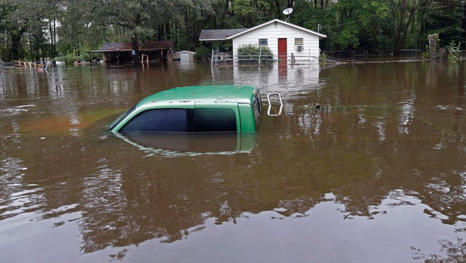 A vehicle and a home are swamped with floodwater from nearby Black Creek in Florence, S.C., Monday. Flooding continues throughout the state following record rainfall amounts over the last several days.