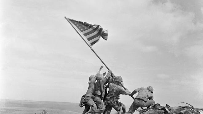 U.S. Marines of the 28th Regiment, 5th Division, raise the American flag atop Mt. Suribachi, Iwo Jima, Japan.