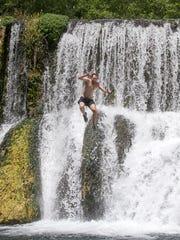 Los más atrevidos se lanzan por la cascada en un espectáculo de adrenalina.
