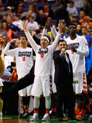 Aquinas graduate Christian White, front, and the Syracuse Orange bench react late in the game. SU won to reach the Sweet 16.