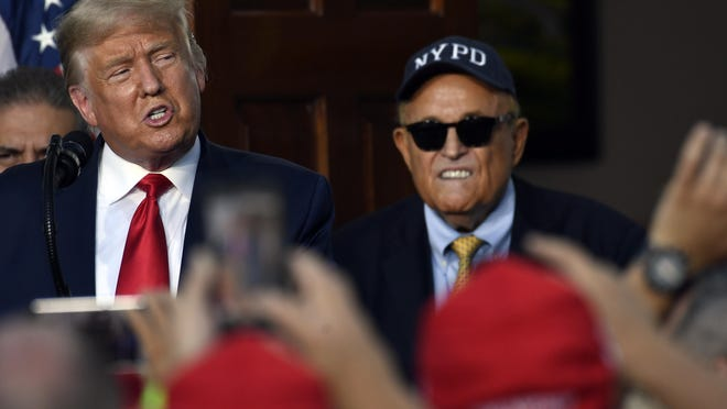 President Donald Trump speaks as Rudy Giuliani, an attorney for President Donald Trump watches, during an event Trump National Golf Club, Friday, Aug. 14, 2020, in Bedminster, N.J., with members of the City of New York Police Department Benevolent Association.