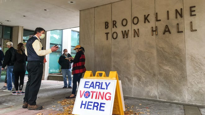 A poll worker ushers in the last people in line for in-person early voting at Brookline Town Hall Sunday before the 1:30 p.m. cutoff.