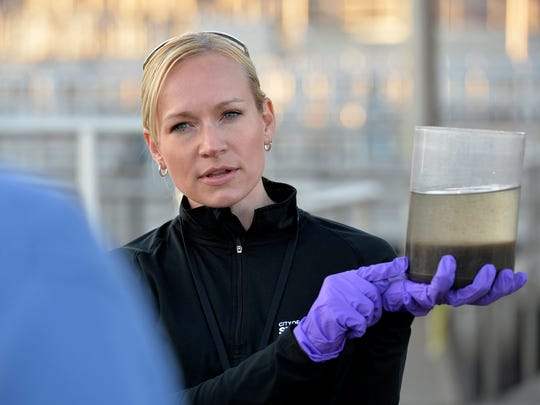 Tracy Hodel, pictured in 2014, holds a sample of wastewater as she explains how solids and liquids are separated in the process during a city council tour of the Wastewater Treatment Facility.