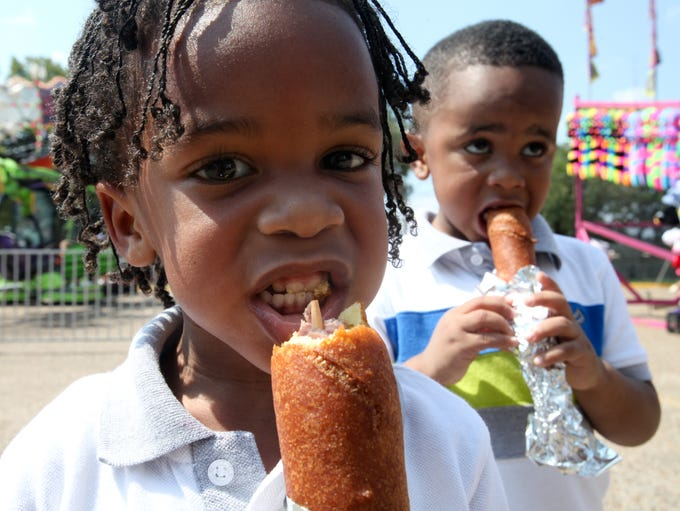 Anthony Holmes, 3, and Isaiah Collins, 4, enjoy corndogs, one of their favorite fair foods, on Saturday at the Ark-La-Miss Fair.