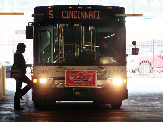 A woman boards a TANK bus bound for Cincinnati at the TANK Transit Center in Covington.
