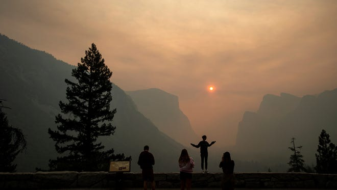 In this July 25 photo Hannah Whyatt poses for a friend's photo as smoke from the Ferguson fire fills Yosemite Valley in Yosemite National Park.